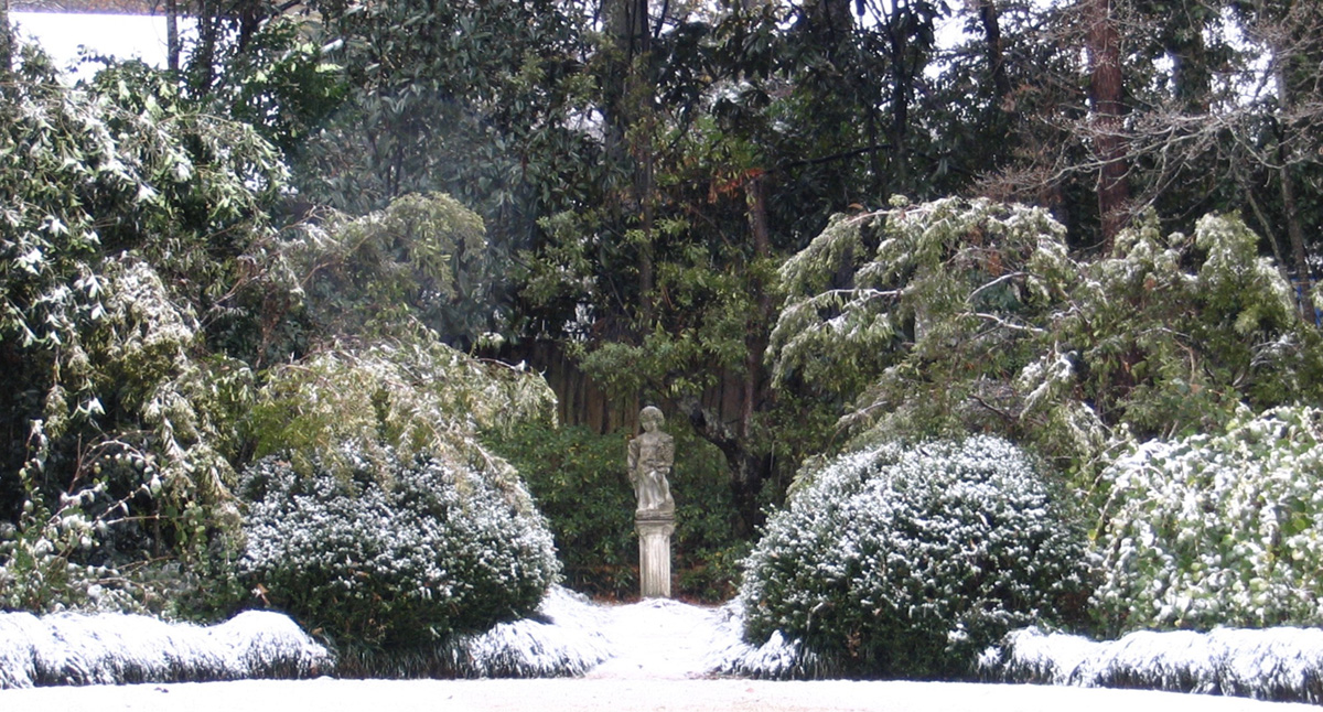 A circular lawn covered in snow winter know, surrounded by garden beds and taller shrubs beyond. A statue of a child, standing on a pedestal where the pushes part, is the focal point. Garden design by Mary Walton Upchurch