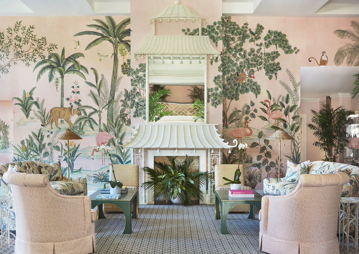 Central seating area in the lobby of the Colony Hotel in Palm Beach, featuring custom scenic wallpaper de Gournay Wallpaper from the lobby's 2021 renovation by Kemble Interiors. The wallpaper depicts flora and fauna native to the area. A symmetrical seating arrangement flanks a white fireplace mantel made to look like a pagoda. The room's color palette includes soft pinks and greens.