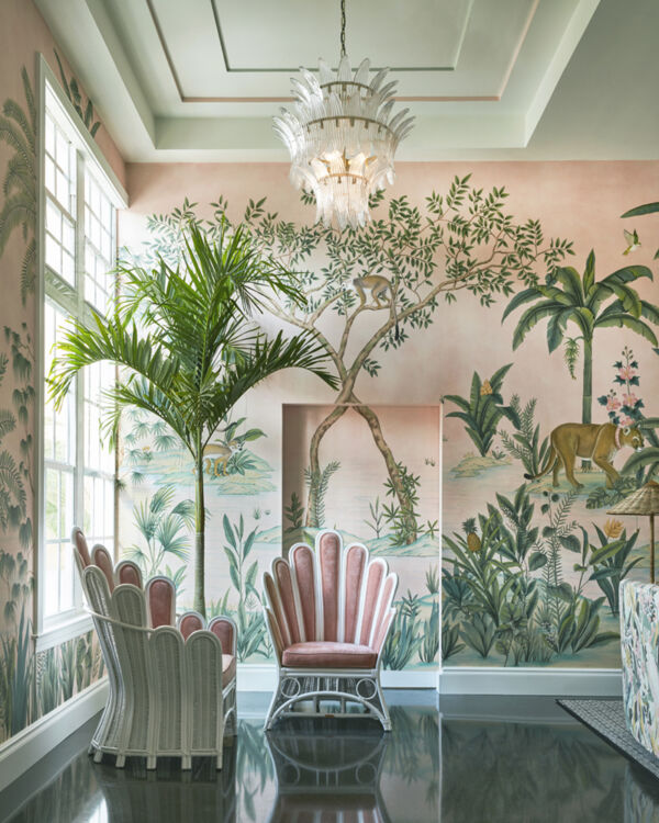 Noir Furniture's King Chandelier hangs from a tray ceiling by a large window. Two whimsically shaped wicker chairs with pink velvet upholstery sit cattycorner on either side of small potted palm tree in the corner. Design by Kemble Interiors, The Colony Hotel 2021