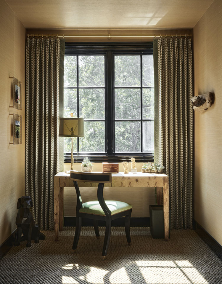 boy's homework desk by a window flanked by green drapes