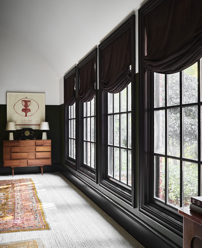 wall of mullioned windows with glossy dark trim and wool flannel Roman shades in a dark, almost black color
