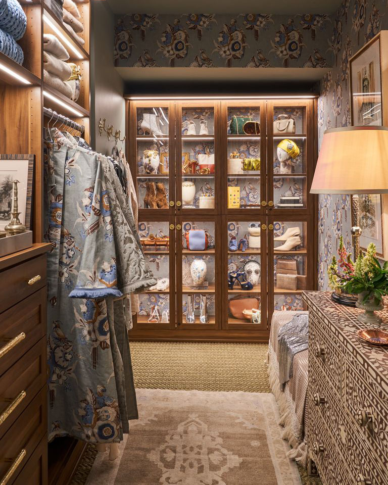 walk-in closet with custom organization unit on back wall, with glass fronted doors displaying the items inside