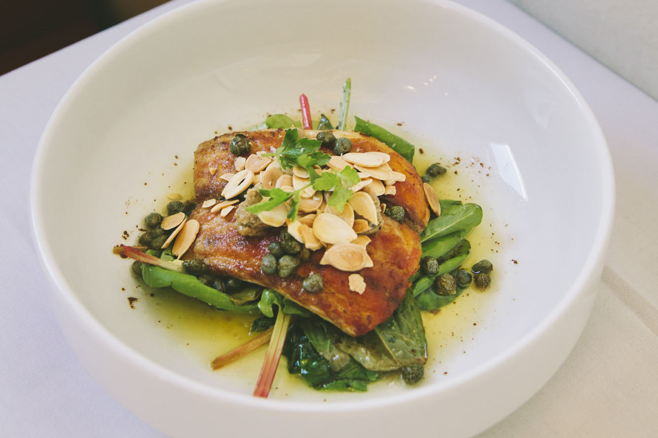 Redfish Almondine, a pan fried fish dish topped with fresh herbs, charred lemon sauce, brown butter, capers, and sliced almonds, from Elvie's, a farm-to-table restaurant in Jackson, Mississippi