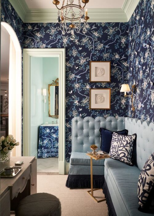 In a space designed by Traci Zeller for the Kips Bay Dallas Showhouse 2020, a dark blue floral print covers the walls of a sitting room and skirts the sink in the powder room beyond, where the walls are a pale blue. The sitting room also features a large, pale blue tufted banquette.