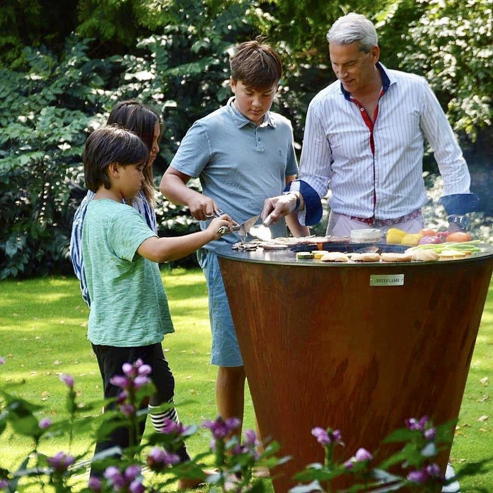 Michiel Schuitemaker, creator of Arteflame grills, with three of is children grill on the circular plancha grill in their LA backyard