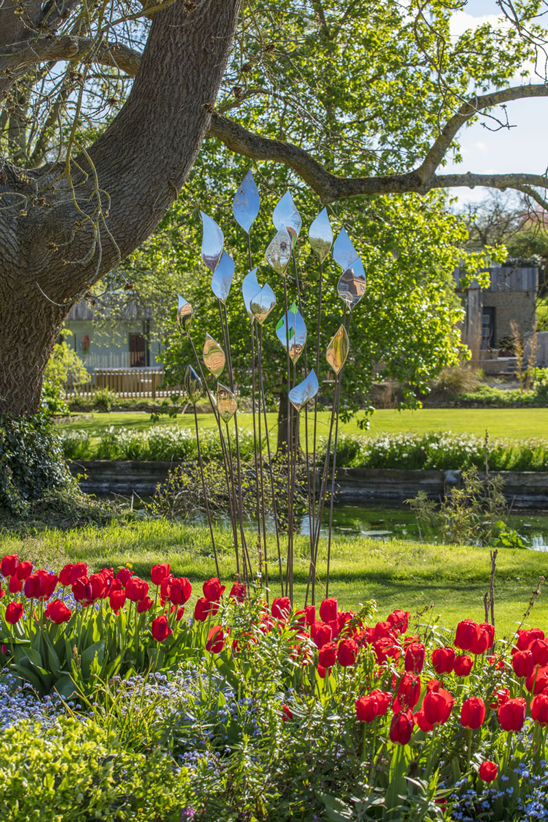 David Harber Sculpture metal leaf sculpture in a bed of red tulips in a garden with a pond and large oak tree