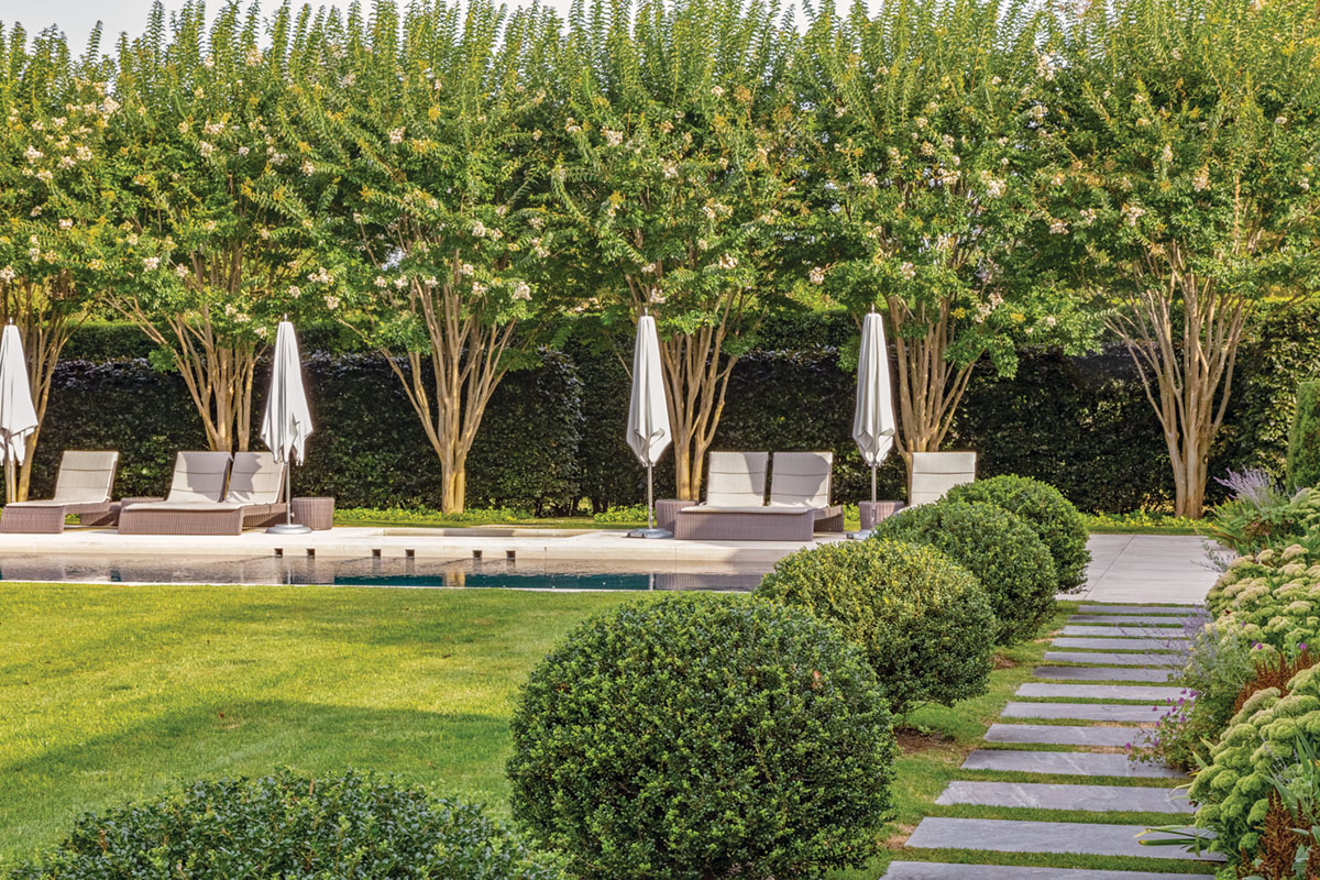A straight path of rectangular stepping stones, bordered by rounded boxwoods, leads to a pool lined by a row of crepe myrtles, landscape architecture by Quincy Hammond