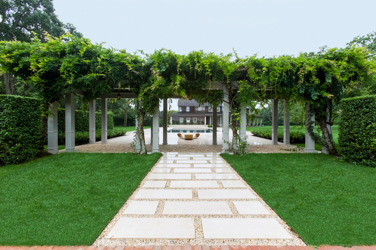 view of a wisteria covered arbor looking with a pool and house beyond in a forma landscape by Quincy Hammond