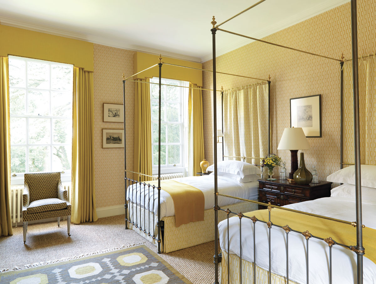 yellow bedroom decorated by Veere Greeney featuring a pair a twin wrought iron canopy beds, and yellow drapes with a tailored valance