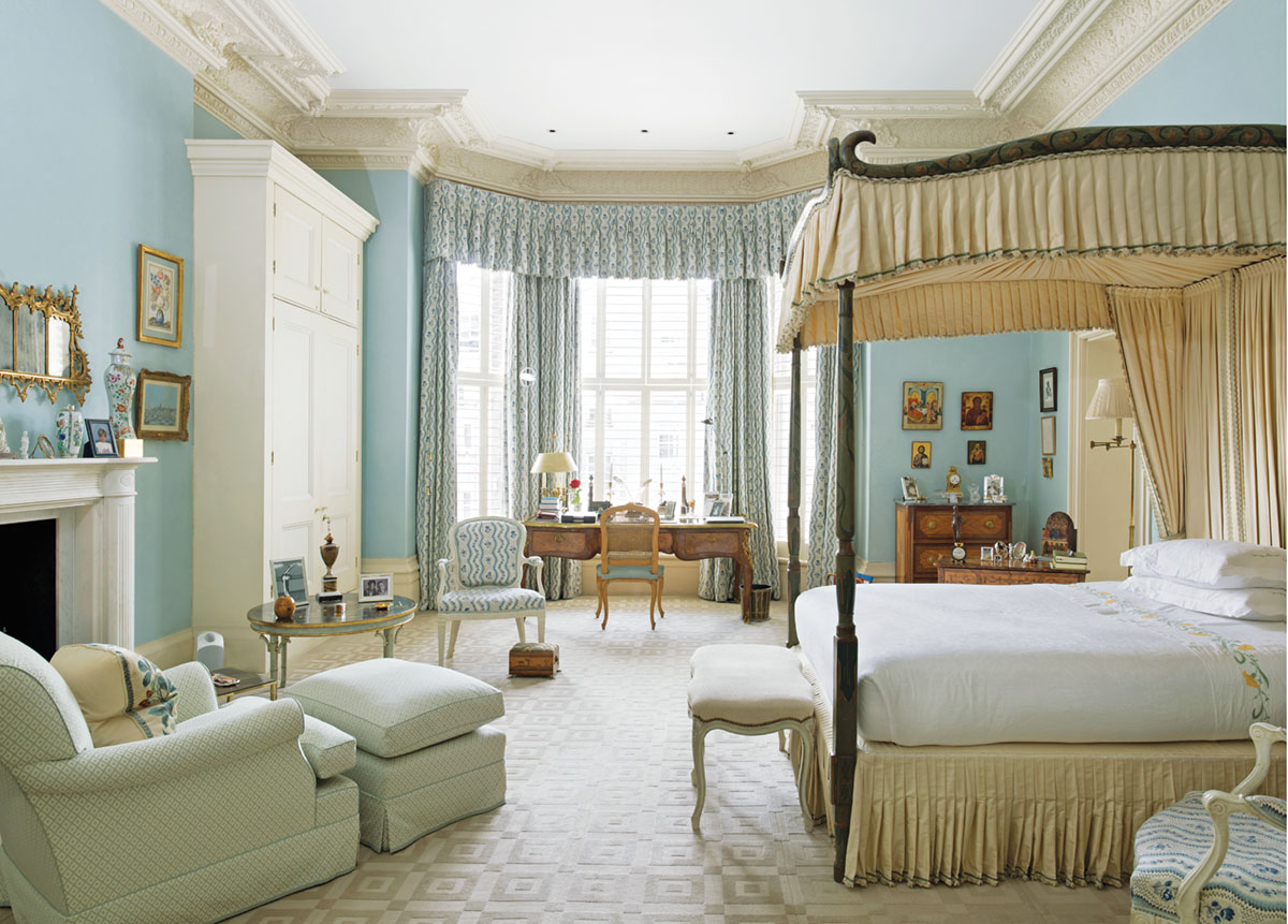 guest room decorated by Veere Grenney with soft blue walls and drapes, upholstered canopied bed in a pleated cream fabric, an antique wood desk and chair by the window and a generously sized club chair and ottoman by the fireplace