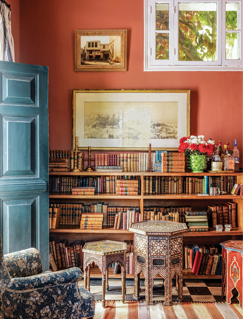 home library with terra-cotta-colored walls and a dusky blue door leading outside
