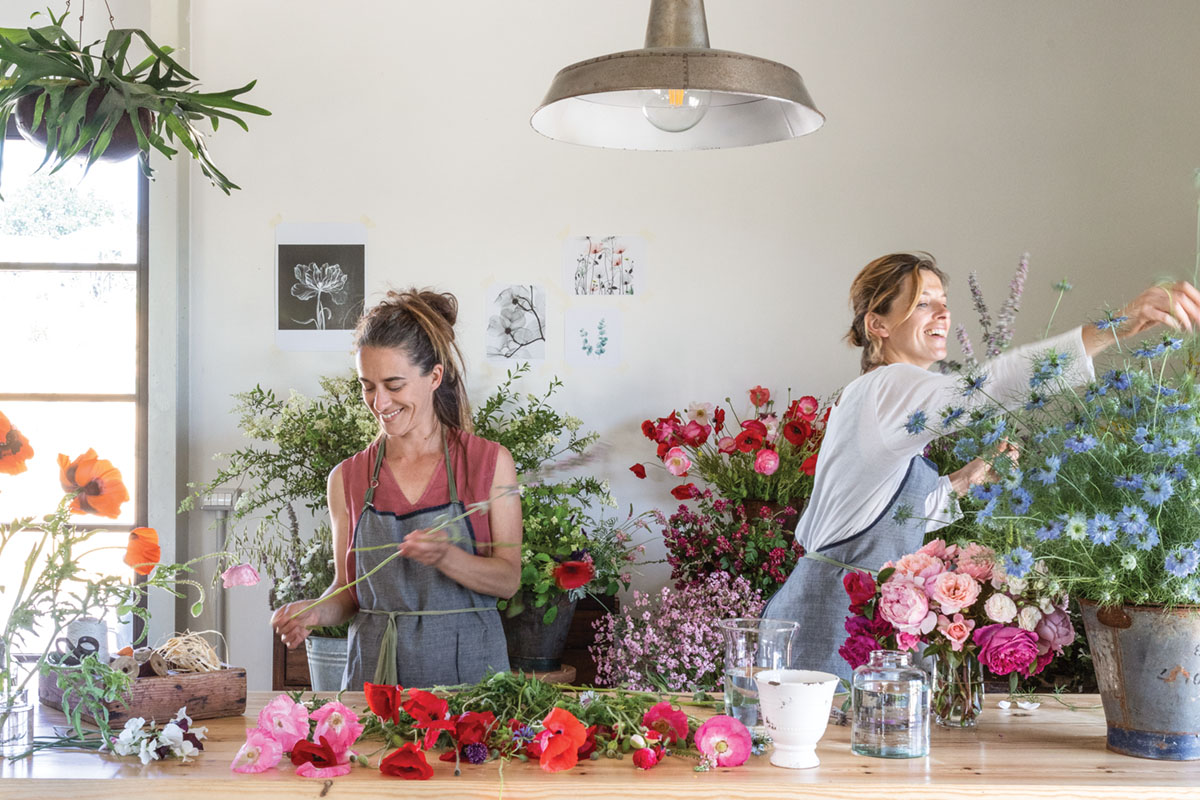 Teresa and Laura Cugusi, owners of PUSCINA FLOWERS, work at a long table filled with flowers.