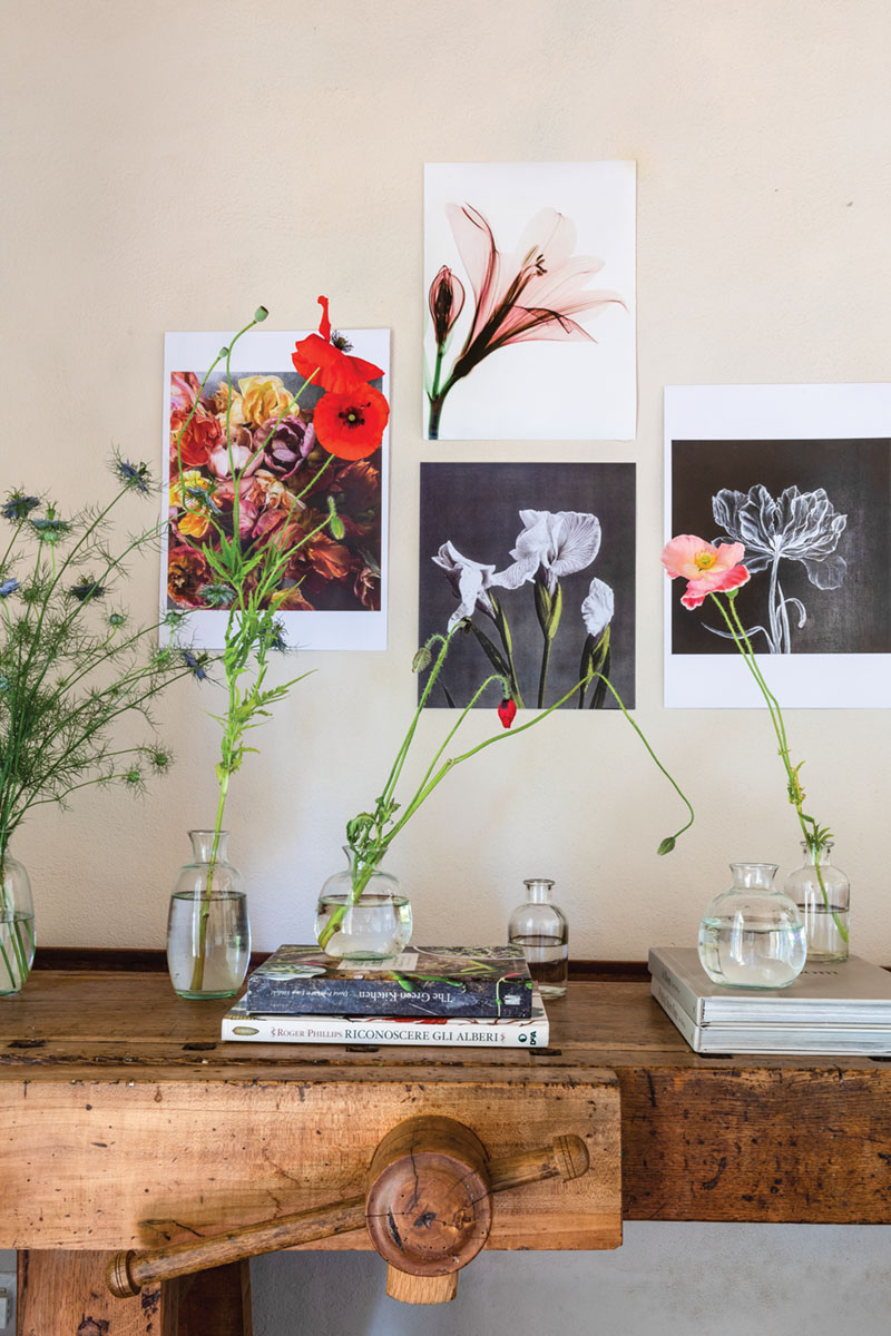 A vignette at PUSCINA FLOWERS includes simple unframed prints of flower photography on the wall, small bottles filled with poppies, and books on an antique wooden table
