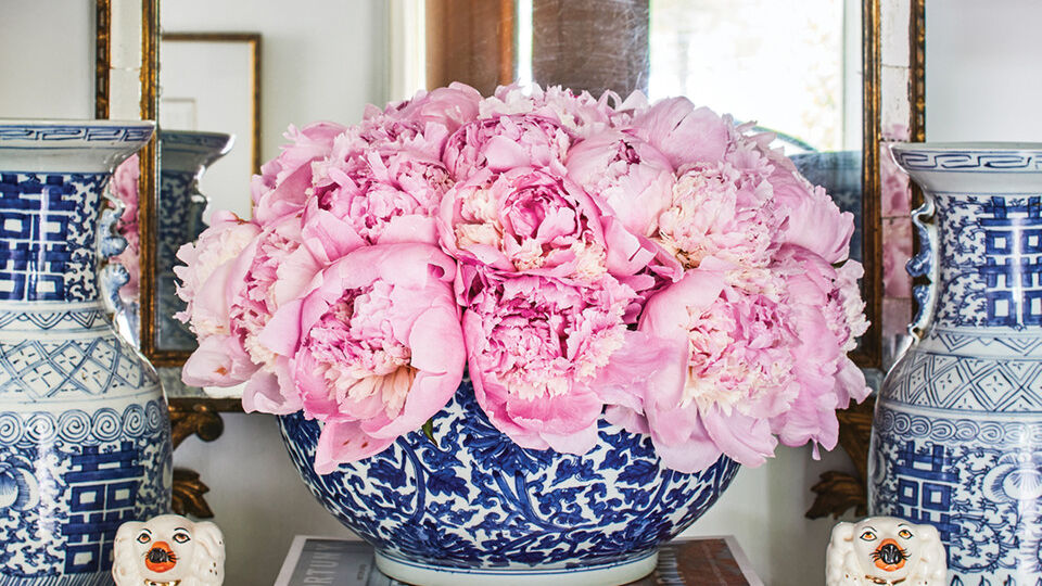 A decorative vignette in Gavin Duke's foyer features pink peonies filling a blue-and-white porcelain bowl, sitting on a stack of books. A pair of porcelain dogs and blue-and-white vases flank either side. In the background is an ornate gilt mirror. The reflection reveals a crystal chandelier and an open, natural wood front door. the walls are painted a soothing cool white.