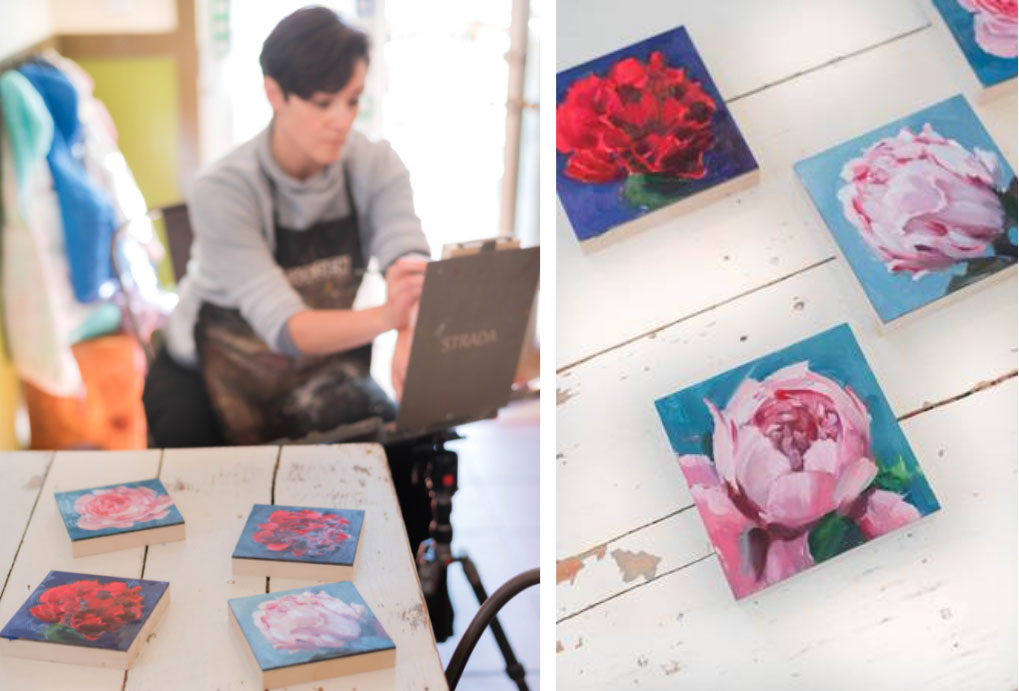 Artist Amy R. Peterson paints at an easel in the background. In the four ground, four paintings of peonies from her Peony Project are displayed on a rustic white table.