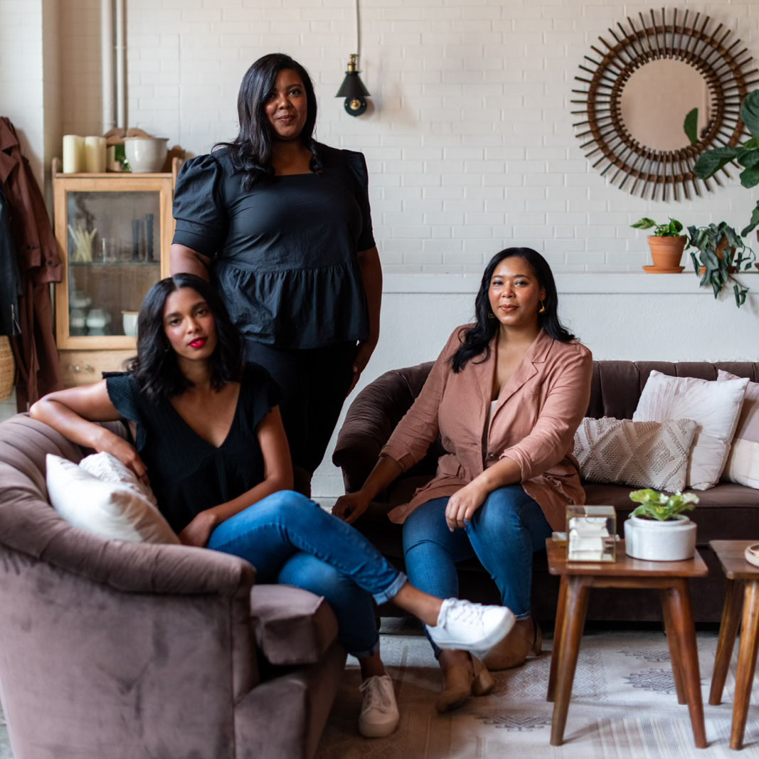 The team of The Wild Mother floral and event design studio. Callie and Leah Palmer sit on a pair a cattycorner sofas in their studio. Lauren, wearing black, stands between them.