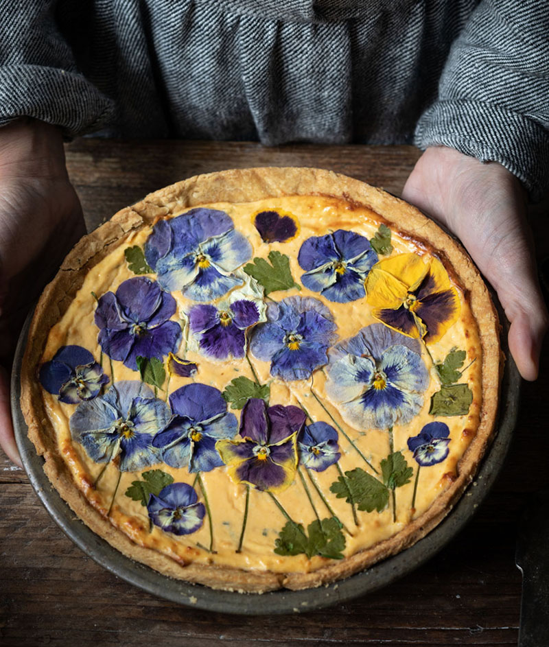 Savory baked cheese tart covered with pressed pansies, an edible flower