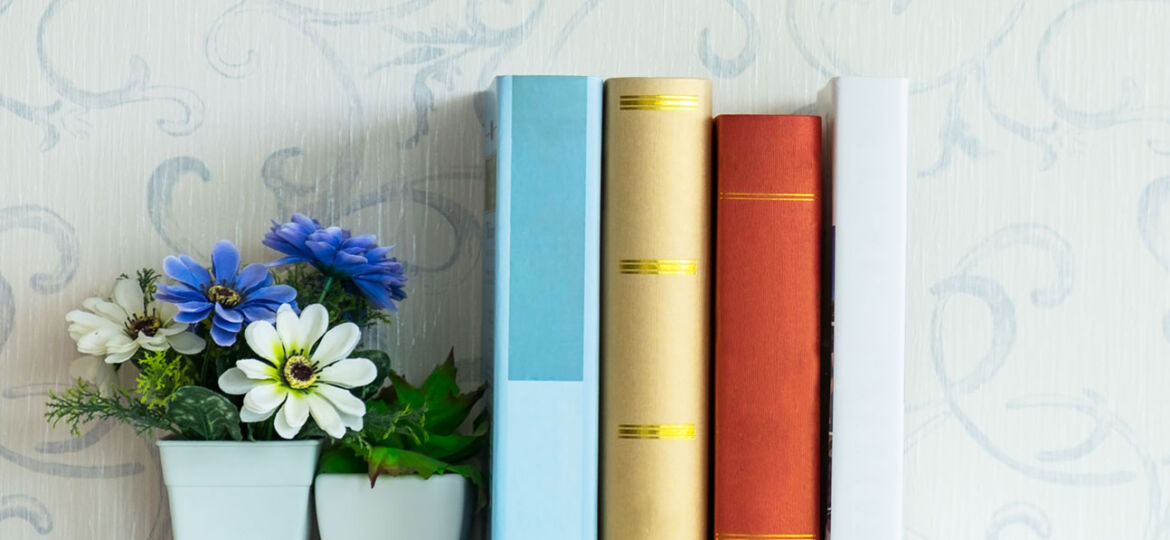 books lined up on a shelf beside a small vase of purple and white flowers