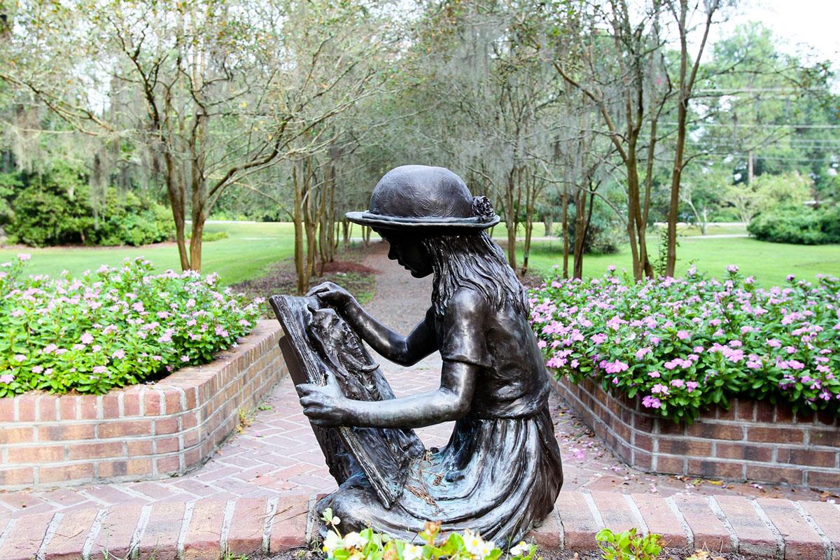 bronze statue of a little girl reading at Azalea Park