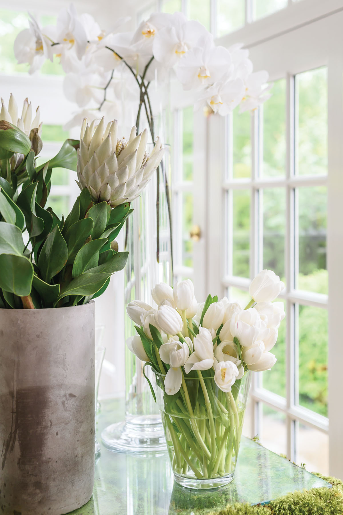 vases of white flowers, arrangement in bunches of a single variety of blooms, including tulips, protea, and orchis