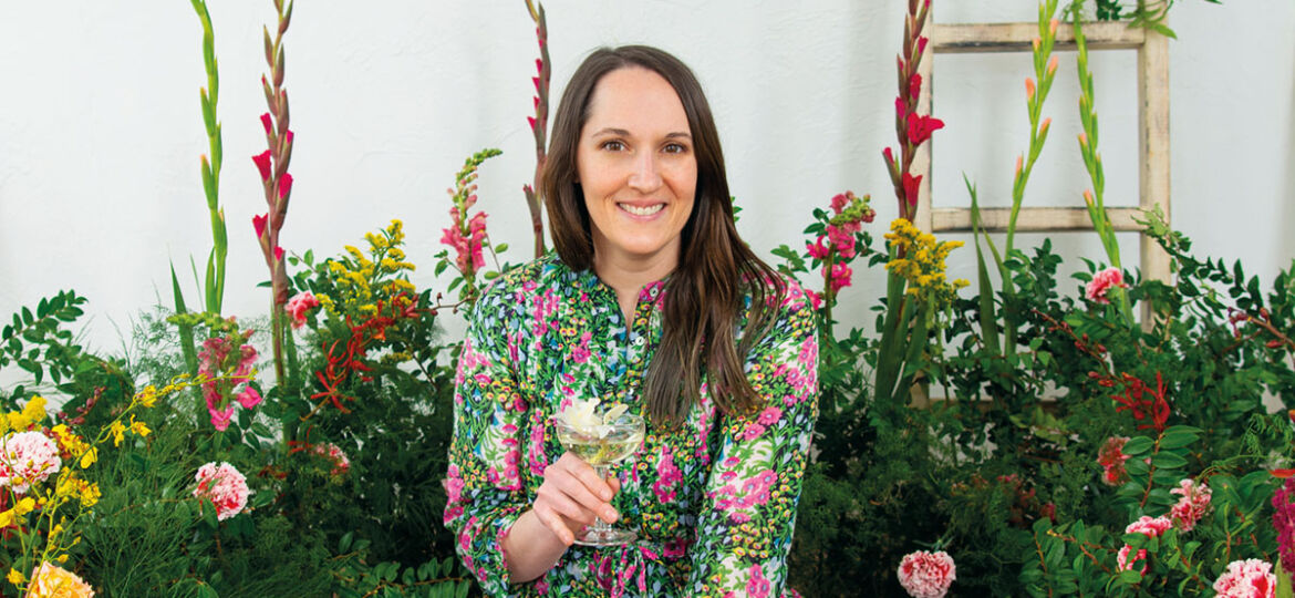 portrait of Alyson Brown, author of The Floral-Infused Cocktail, wearing a floral dress, surrounded by a lush floral installation, holding a cocktail in her hand