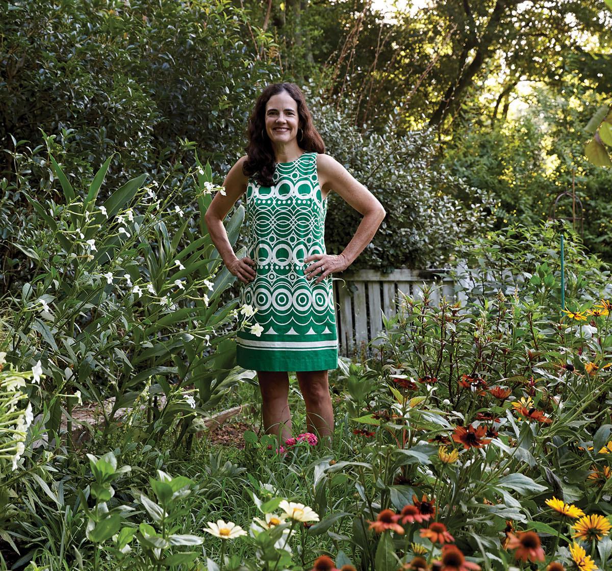 Floral designer Kappi Naftel stands in an abundant summer flower garden. She wears a green and white patterend sleeveless shift dress