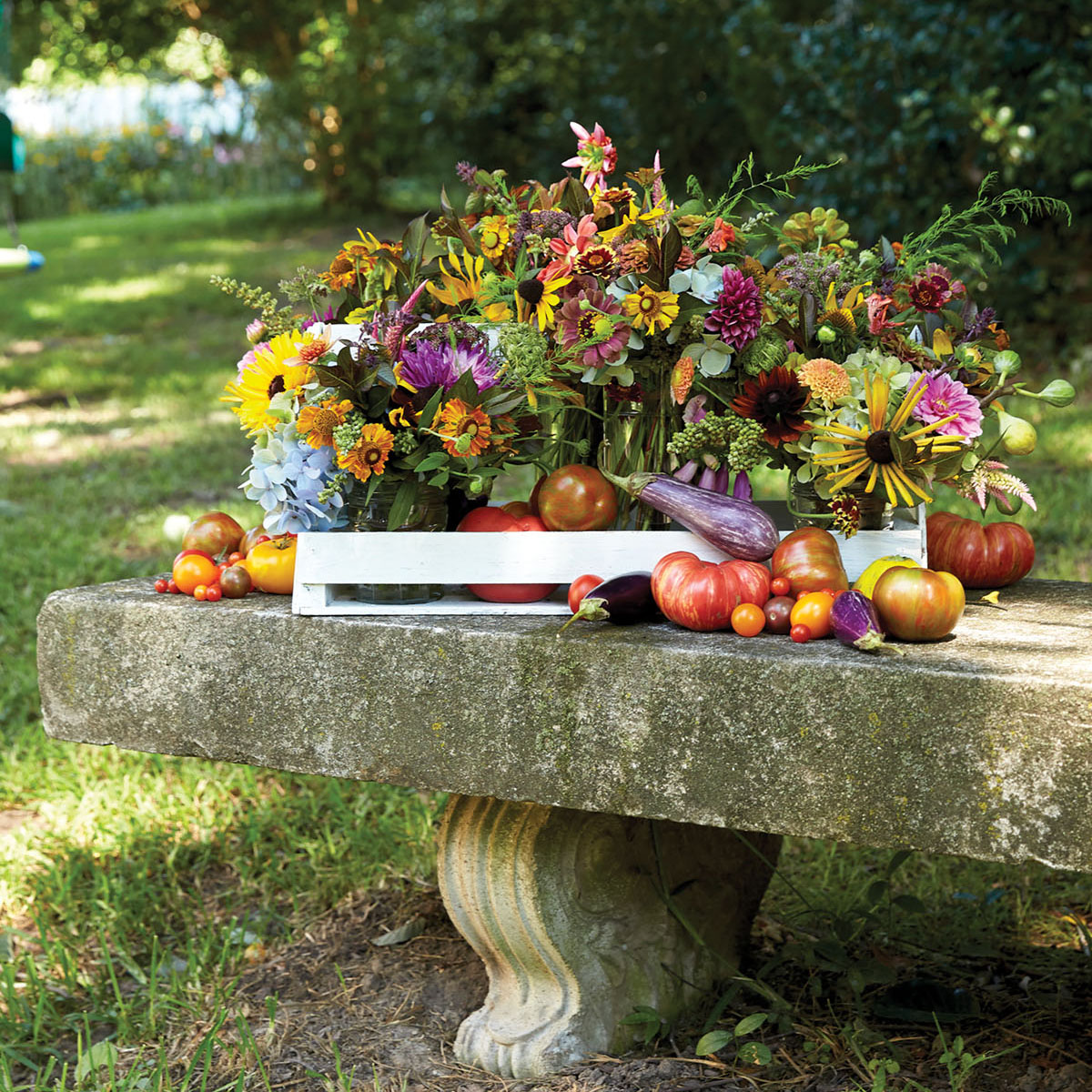 A summer arrangement by Birmingham, AL floral designer Kappi Naftel of Kap Flowers featuring individual bouquets in assorted glass containers, placed a white wooden handheld container and decorated with eggplants, tomatoes, and other summer vegetables. It is displayed on old concrete garden bench in a shady garden