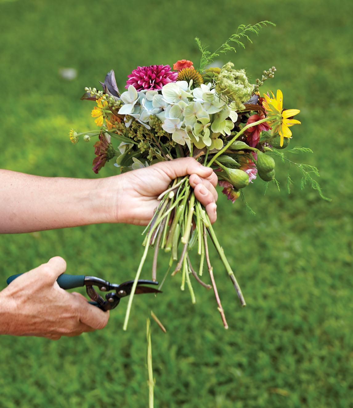 Kappi Naftel uses clippers to trim bouquet stems