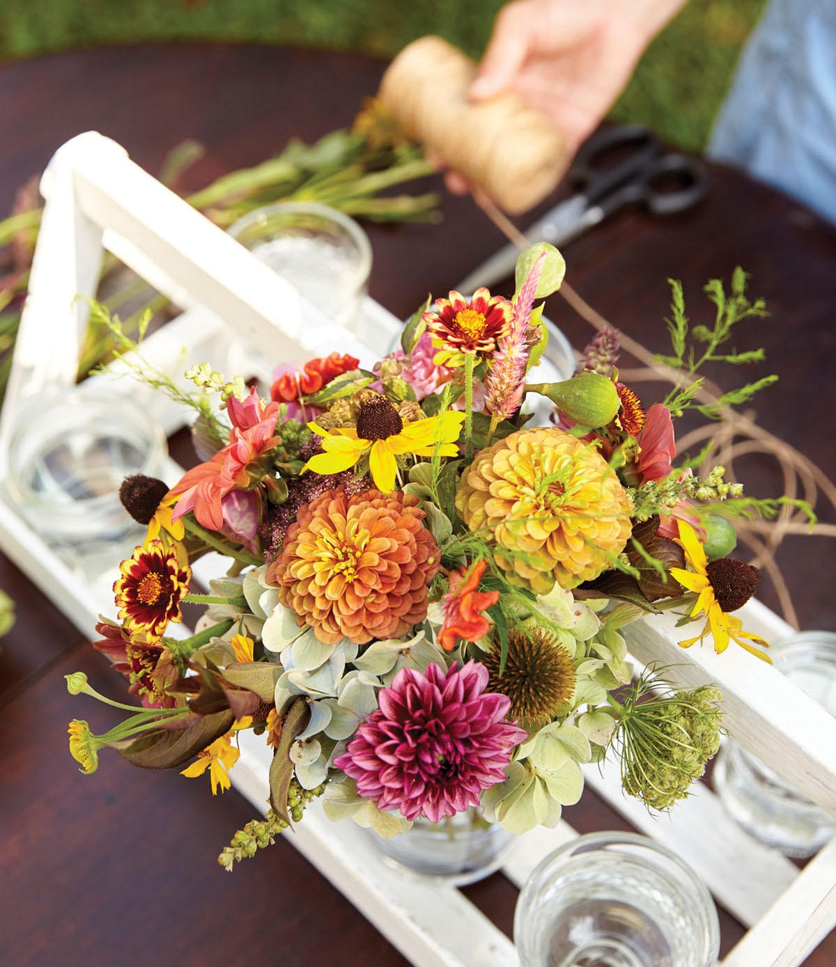 A shallow, flat white tray with a handle across the length of the top is filled with glass containers. Some are filled with bouquets.