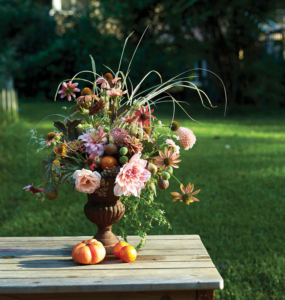 peach, pink, green, and rust-colored summer arrangement by Birmingham, AL floral designer Kappi Naftel of Kap Flowers. The vessel is a rust-colored urn, which sits on a picnic table alongside summer tomatoes, with an expanse of green lawn in the background