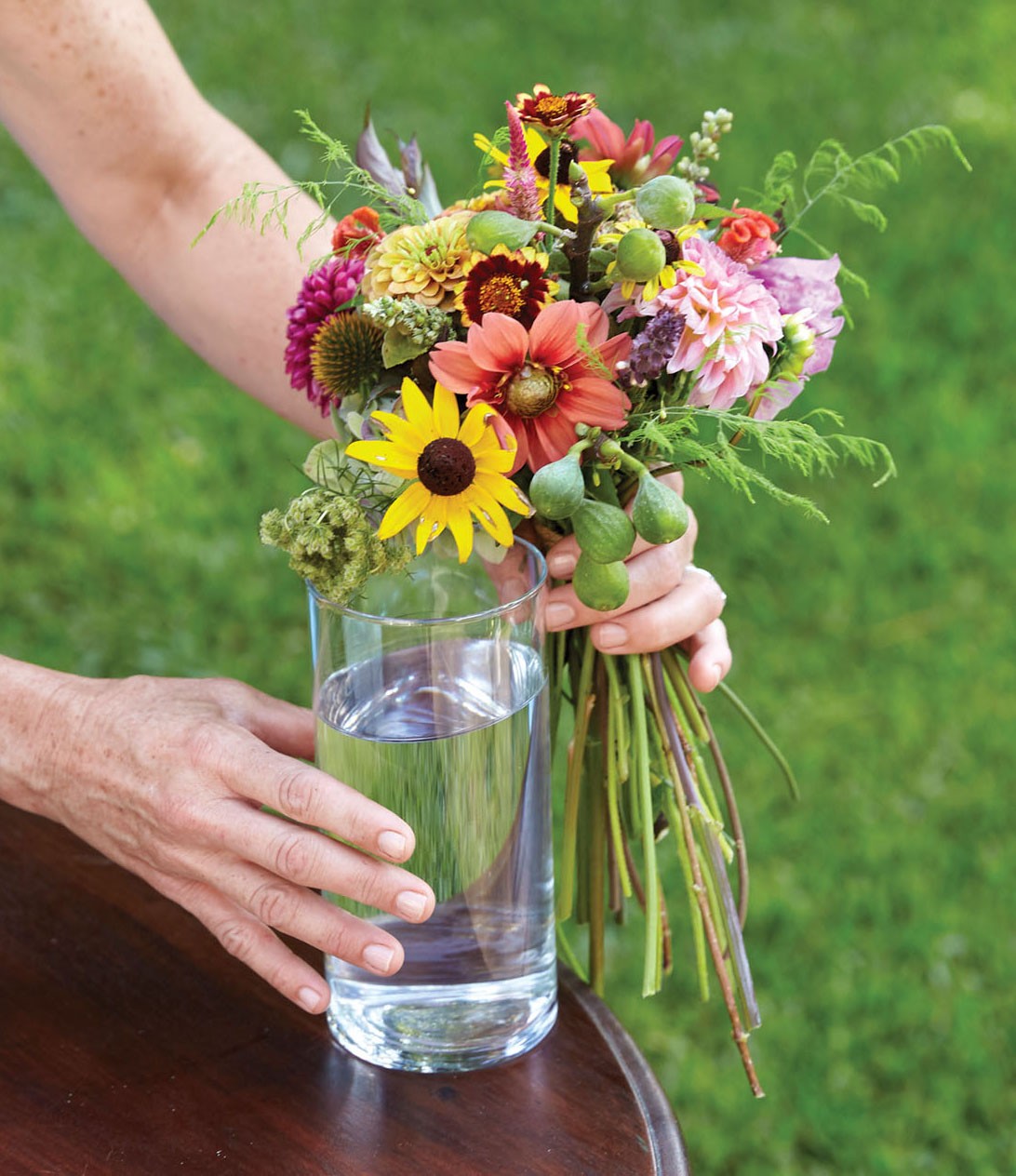 Kappi Naftel holds her bouquet against a glass to judge stem length. The bind point is near the top of the vessel.