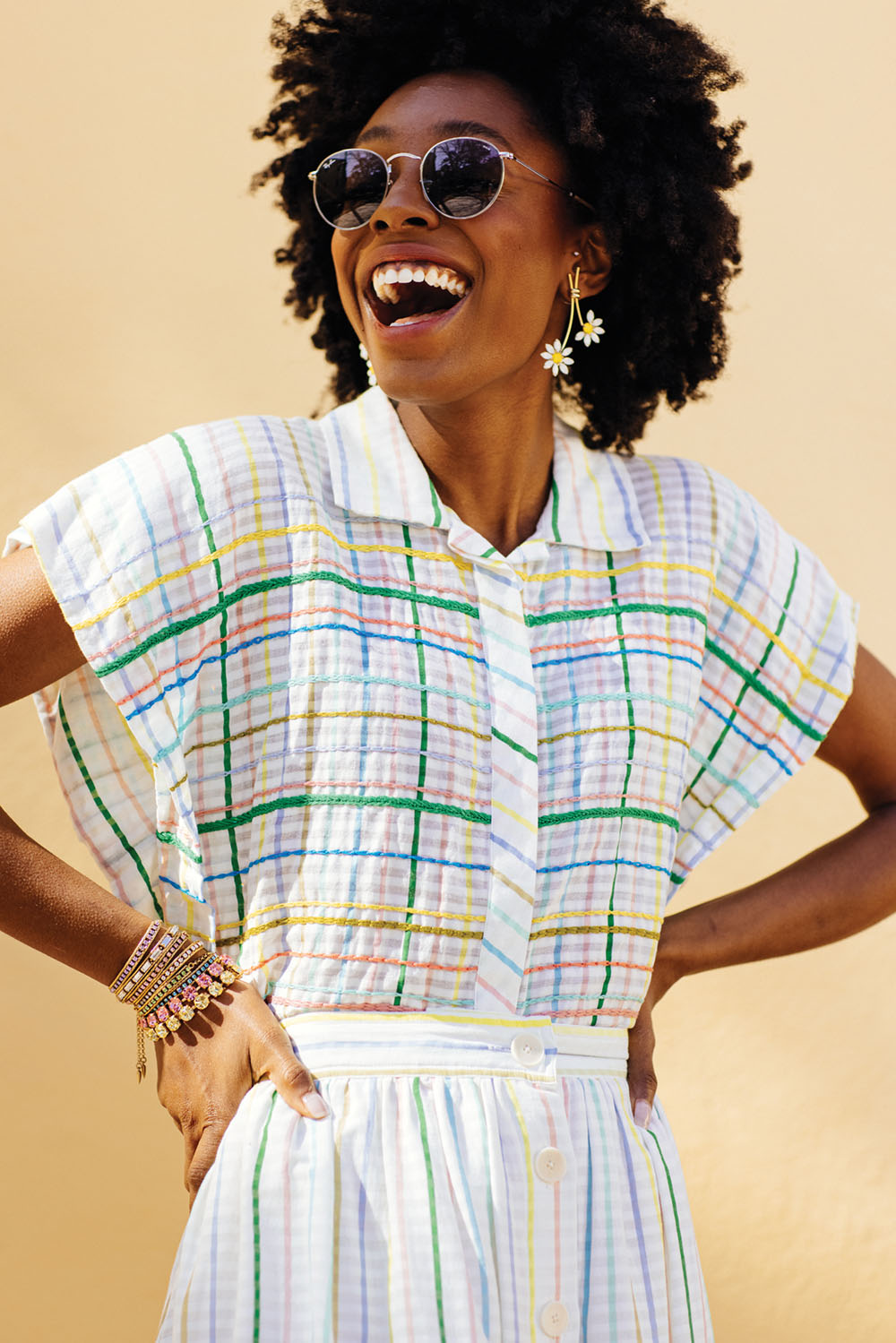 floral earrings worn by a model wearing a cotton summer dress in a green, pink, blue, and, yellow large-scale plaid on a white background