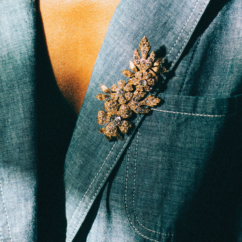 floral brooch with gold-toned metal and clear stones, costume jewelry by Lauren Hope