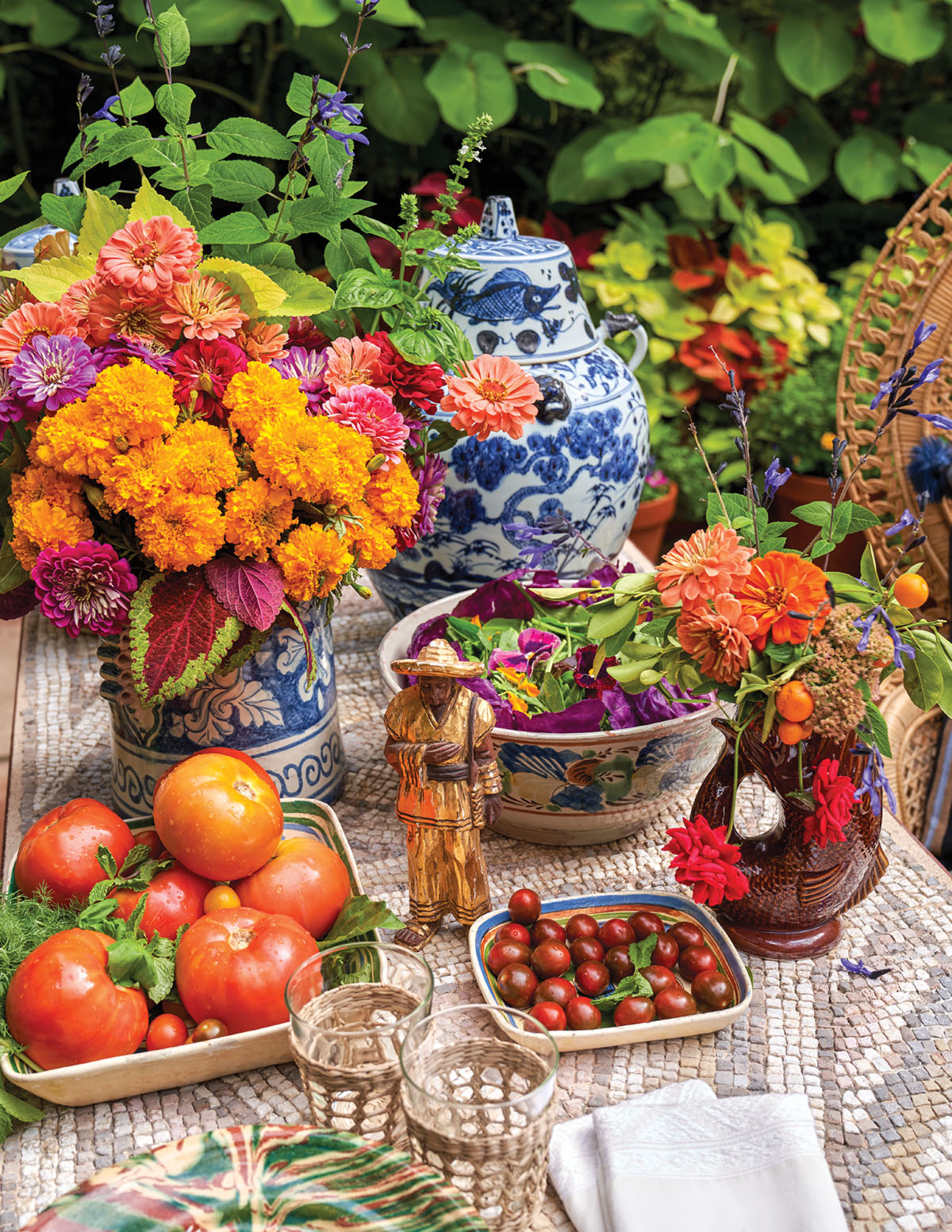 A blue-and-white ginger jar, a large salad, shallow bowls of summer tomatoes, and a pair of lush red and orange floral arrangement fill a mosaic patio table