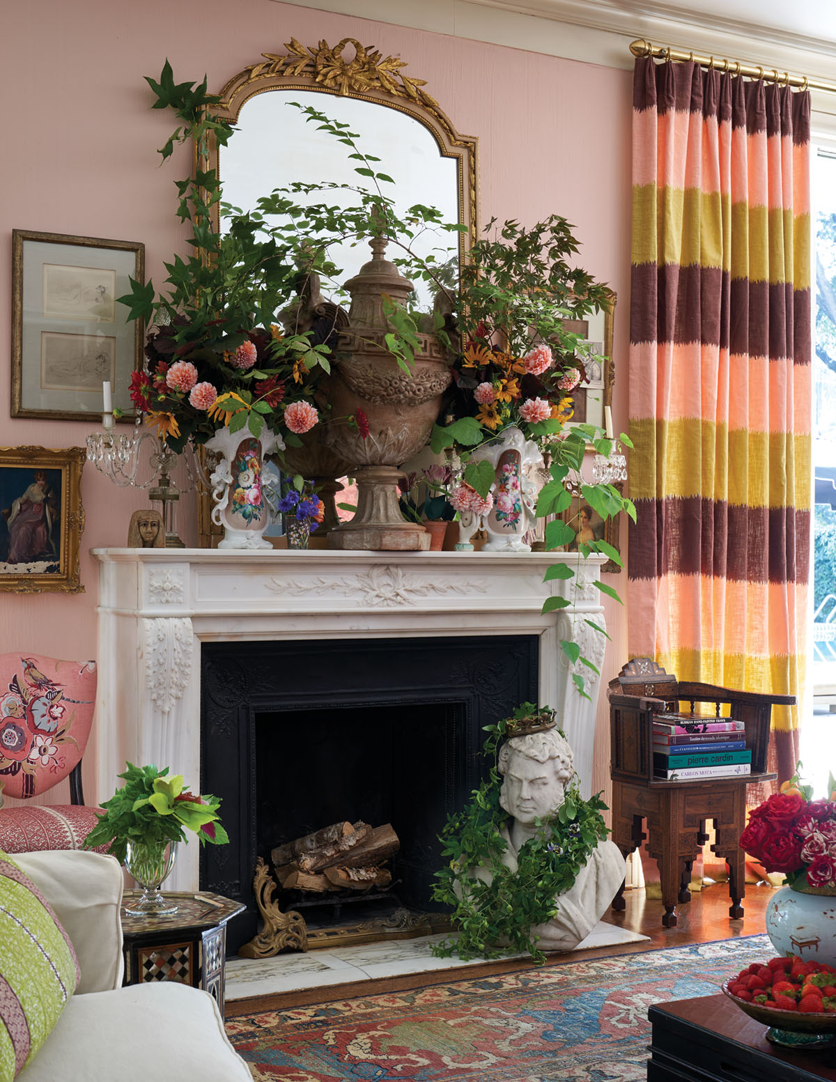 Michelle Nussbaumer's house, mantel covered in vases of lush floral arrangements, gilt mirror, pink walls, oriental rug, and drapery panels with horizontal strips of pink, green, and chocolate brown