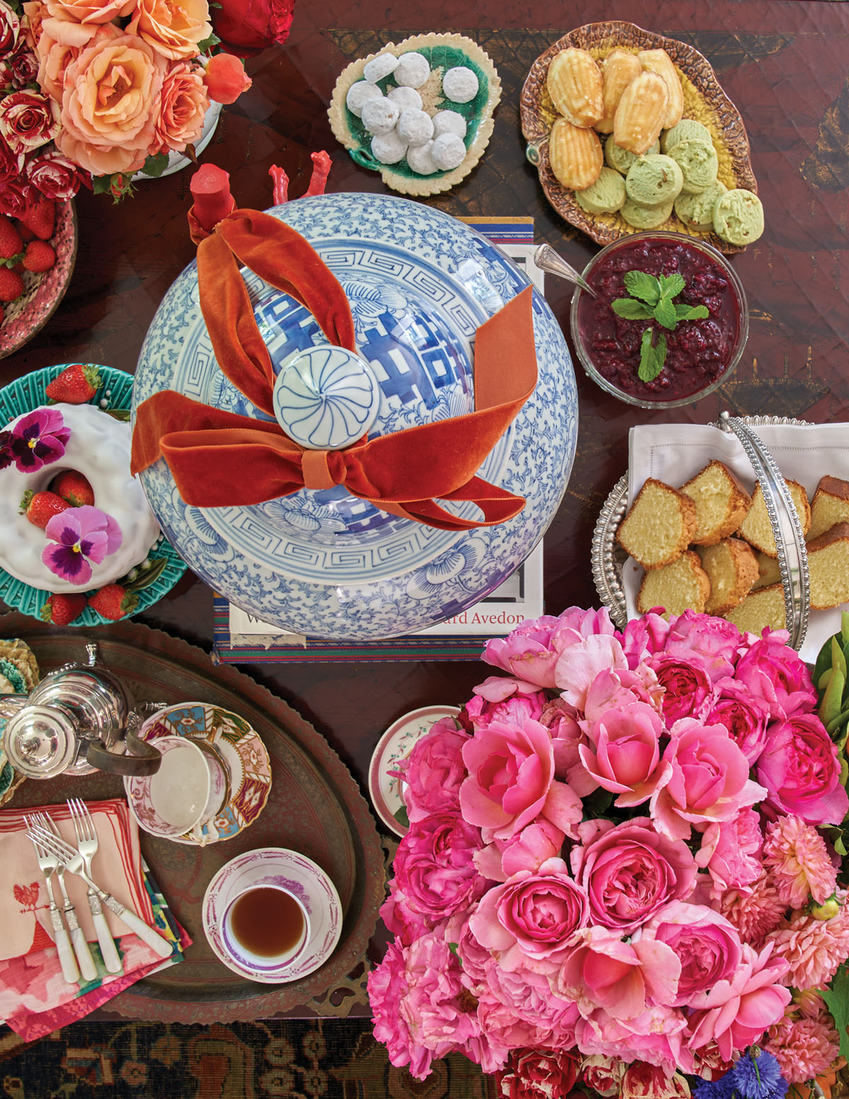 overhead view of the dessert table, including a bouquet of pink roses and a lidded blue-and-white chinoiserie jar