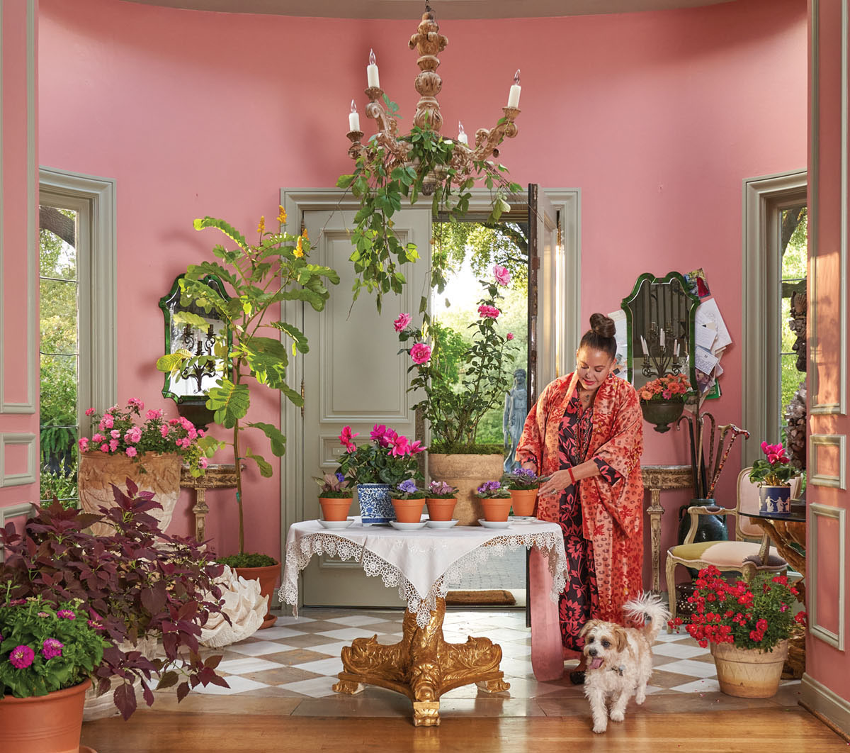 Wearing luxurious, brightly colored pajamas and robe, designer Michelle Nussbaumer stands in her entry hall, painted pink and filled with house plants. She tends to potted plants on her entry table. Her dog stands at her feet.