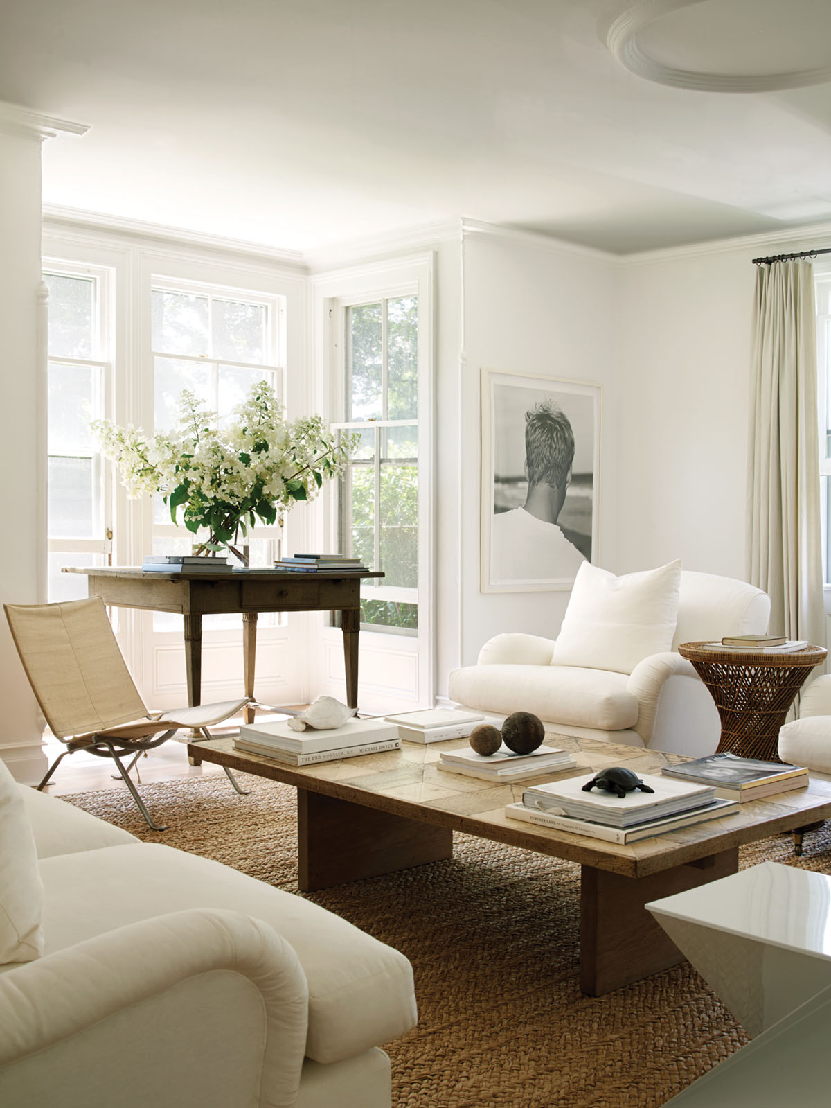 a mix of midcentury and antique furniture in a white and neutral living room decorated by Mona Nerenberg. A large garden-style arrangement of white blooms adorns an antique wood table placed in a nook created by a bay window
