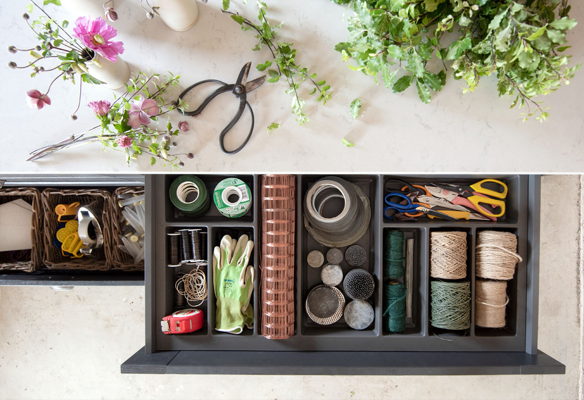 An overhead view of a work table, strewn with flowers. Two open drawers reveal spools of string, clippers, a roll of chicken wire, pin frog, rubber bands, work gloves, water tubes and other floral design tools neatly organized in compartments