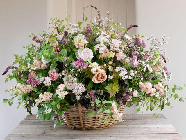 large garden style arrangement in a basket by British floral designer Philippa Craddock