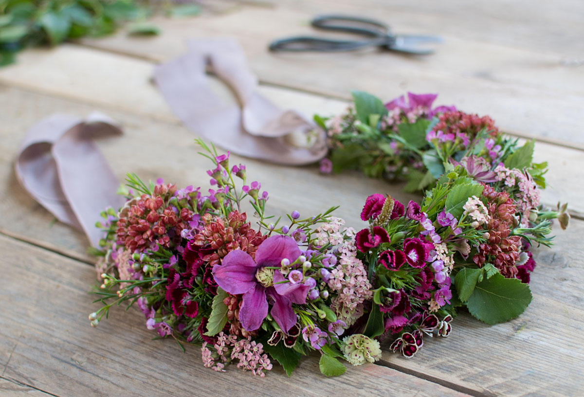 Flower crown be Philippa Craddock featuring flowers in a range of purple/violet tones, with pale lavender ribbon ties