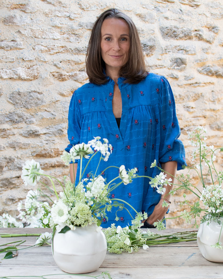 Philippa Craddock, wearing a bright blue top, stands beside loosely arranged white flowers in white pottery vases