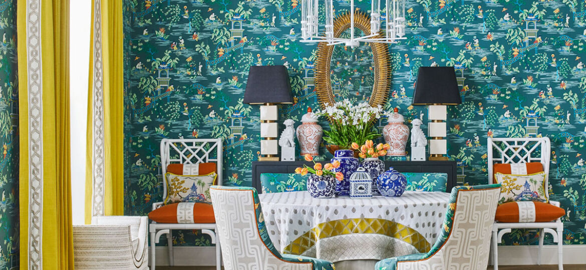 Vibrant dining room featuring teal botanical wallpaper, bright yellow curtains, chinoiserie and geometric patterns from the Stroheim Color collection