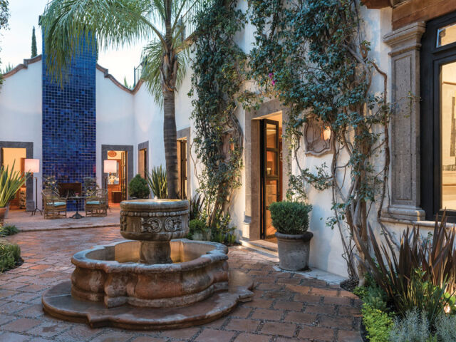 a fountain and terra cotta patio surrounded by white stucco one-style buildings and tropical plantings at Hotel Amparo