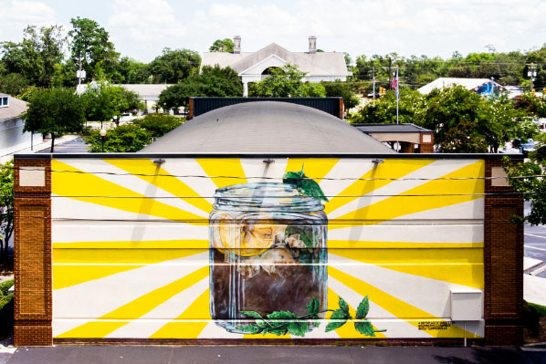 The birthplace of sweet tea mural, featuring a large jar of iced tea radiating yellow rays in Summerville, South Carolina