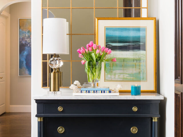 hallway vignette with chest, mirror, lamp, and artwork