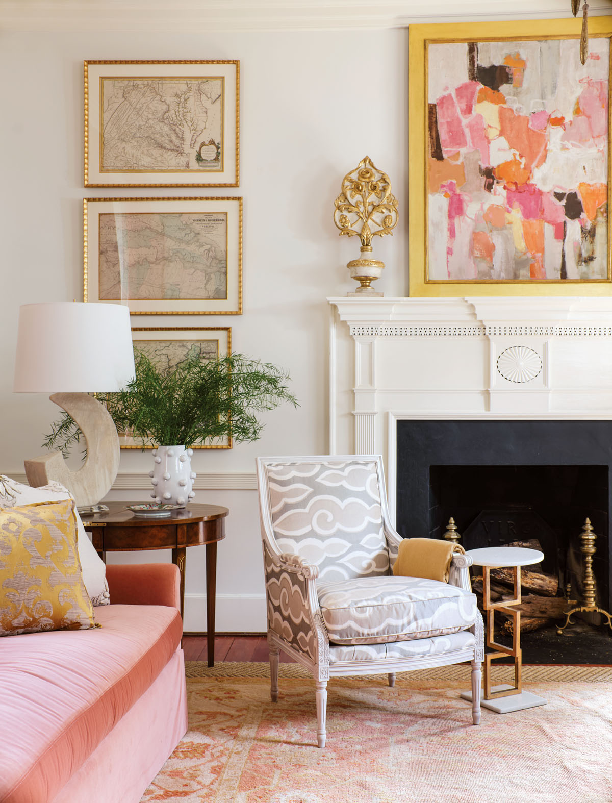 a colorful abstract painting hangs above a painted white mantel.