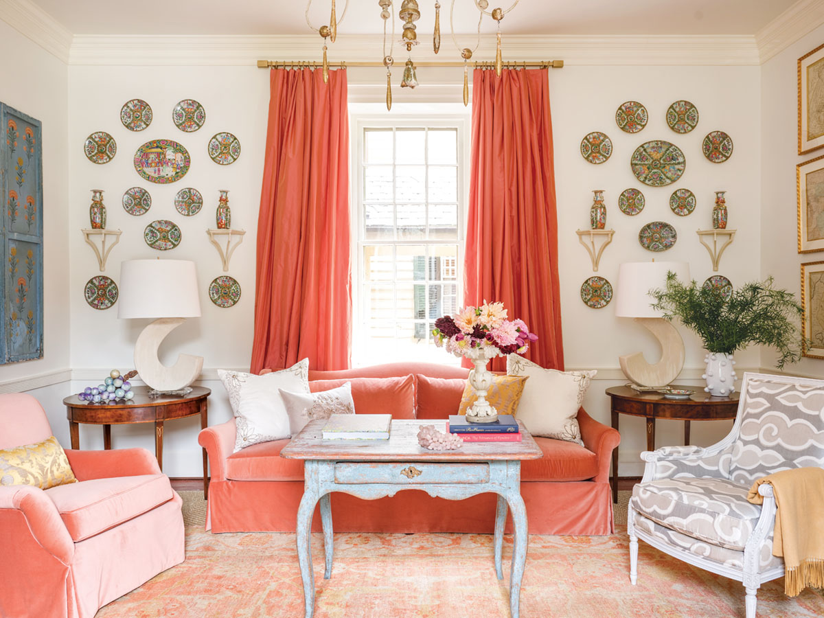 living room designed by Janie Molster, velvet sofa and club chair, plate hanging, coral color decor scheme