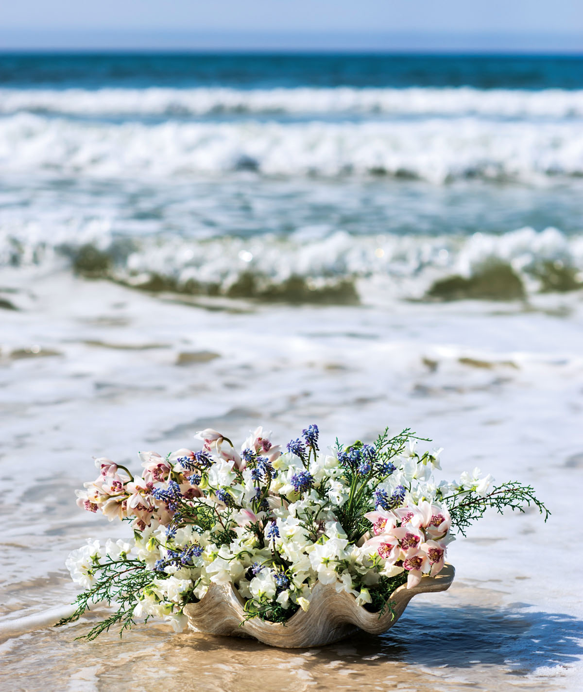 large half shell filled with flowers set on the shore with waves and blue sky in the background