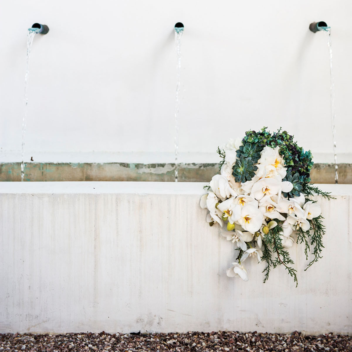 white orchid and succulent bouquet set on the side of a white stucco fountain trough. Behind it, water flows from three wall-mounted spigots